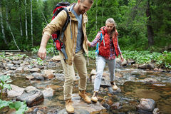 Traveling together. Young travelers with backpacks walking down stone-path in the river Stock Photo