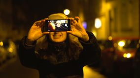 Girl is making a selfie photo in a night city on the street. Traveling tourism and visiting cities stock footage