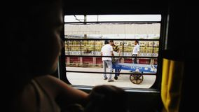 Traveling on train in india. Kolkata, India - December 2016,people walking on railway station close-up view through train window stock video