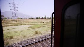 Traveling on train in india. View through door moving train traveling through indian landscape stock footage