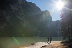 traveling Twee mensen die onder het blauwe meer lopen stock foto's