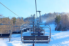 Traveling up the mountain in the ski lift. A sunset winter landscape of a skiing resort Stock Photos