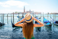 Traveling in Venice. Young female traveler enjoying beautiful view on venetian chanal with gondolas and San Giorgio Maggiore island in Venice Royalty Free Stock Photography