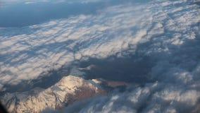 traveling Visión desde la ventana del aeroplano Opinión sobre las montañas Nubes de la pluma almacen de metraje de vídeo
