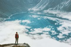 Traveling woman above clouds and lake in mountains Stock Image