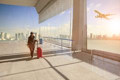 Traveling woman with belonging luggage walking in airport terminal building and passenger plane flying over building in city stock photography