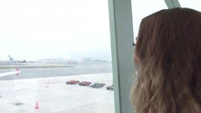 Traveling woman looking to airport terminal window on airplane in departure lounge. Woman tourist looking to window stock video footage