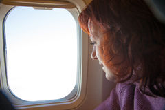 Traveling. Woman is sitting in the airplane. Royalty Free Stock Photo