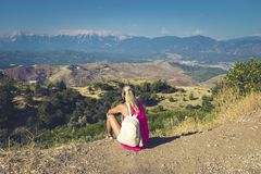 Traveling woman sitting near mountain and looking far away.  royalty free stock image