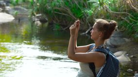 Traveling woman using mobile phone for photo while hiking in jungle forest. Woman tourist shooting video on smartphone. While climbing on river in rainforest stock footage