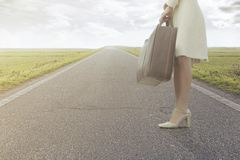 Traveling woman waits with her suitcase to leave for a new journey. Traveling woman waiting on the roadside with her suitcase to leave for a new journey Royalty Free Stock Images