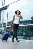 Traveling woman walking with suitcase and mobile phone Stock Images