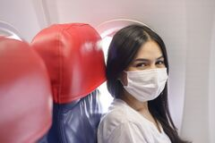 Traveling woman is wearing protective mask onboard in the aircraft, travel under Covid-19 pandemic, safety travels, social