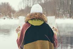 Traveling woman in winter clothes, standing in front of the lake in the winter forest with a map of the foggy morning. Wanderlust. Side view Royalty Free Stock Image
