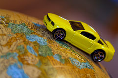 Traveling The World. Concept of world travel. A Toy car on a globe of the earth. (Focus on car royalty free stock image