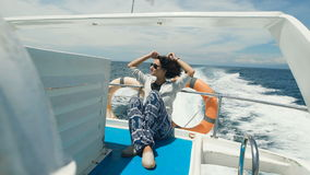 Traveling on a yacht on the Indian Ocean on the island of Bali. The girl brunette on a yacht resting and spending his. Traveling yacht the Indian Ocean on the stock footage