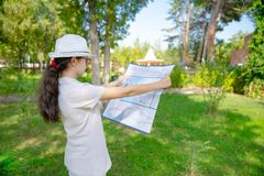 Traveling young girl with map, finds the way and direction. Young girl doing cultural trip historic shrine in the garden royalty free stock images