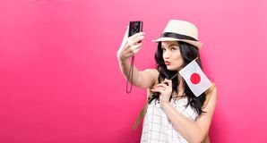 Traveling young woman holding a camera with Japanese flag. On a solid background Stock Photo