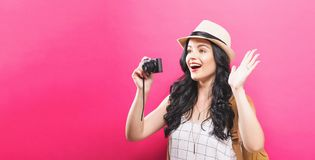Traveling young woman holding a camera. On a solid background Royalty Free Stock Photo