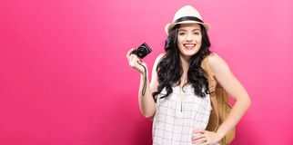 Traveling young woman holding a camera. On a solid background Royalty Free Stock Images