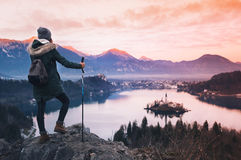 Traveling young woman looking on sunset on Bled Lake, Slovenia,. Travel Slovenia, Europe. Woman looking on Bled Lake with Island, Castle and Alps Mountain on stock photos