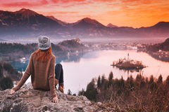 Traveling young woman looking on sunset on Bled Lake, Slovenia,. Travel Slovenia, Europe. Woman looking on Bled Lake with Island, Castle and Alps Mountain on Royalty Free Stock Photography