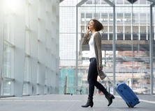 Traveling young woman with mobile phone and suitcase. Full length side portrait of a traveling young woman with mobile phone and suitcase Royalty Free Stock Photography