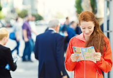 Traveling young Woman reading a Map. Closeup portrait, shot of beautiful Traveling young Woman reading a Map, isolated busy city street background. Travel life Stock Photos