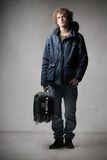 Traveller. Young man carrying a trolley case Royalty Free Stock Photography