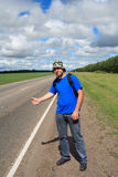 Traveller. Man costs on a roadside of road and stops gesture passing machines Stock Photography