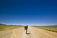 Traveller with backpack on a lonely road in desert Stock Image