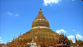 Traveller and Burmese people come to Shwezigon Pagoda at Bagan in Mandalay, Myanmar. The Shwezigon Pagoda or Shwezigon Paya  is a Buddhist temple located in stock video footage