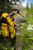 Traveller with camera. In mountains stock photography