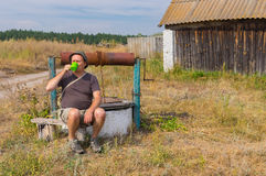 Traveller drinking water at country draw-well Stock Photography