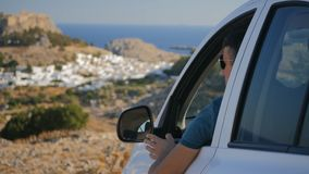 Traveller enjoys the panoramic view. From his car, turns and shows OK stock video footage
