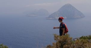 Traveller enjoys the panoramic view. Traveller enjoys the view to an unhabited islands in Gelidonya cape in Mediterranean sea, Antalya, Turkey. Windy weather stock video footage