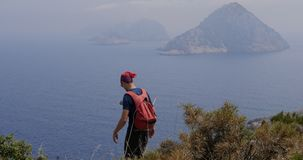 Traveller walking down the hill. Traveller enjoys the view to an unhabited islands in Gelidonya cape in Mediterranean sea, Antalya, Turkey. Windy weather stock video