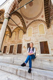 Traveller female sitting in the courtyard of the Mosque. Traveller female sitting in the courtyard of the Mosque in Istanbul and enjoy the architecture of the Stock Photo