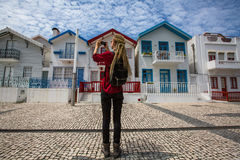 Traveller girl with blonde dreadlocks is takes photo on a smartphone striped houses in Costa Nova Royalty Free Stock Photos