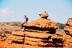 A traveller sitting on a rock in the South African Magaliesberg. A traveller girl sitting on a fantastically nature shaped yellow rock in the South African Stock Image