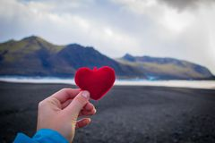 Traveller holding a plush heart in Vatnajökull National Park, Iceland, Europe. royalty free stock images