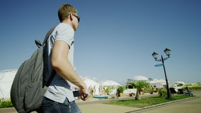 Traveller holding selfie stick and walking. Happy traveller holding selfie stick. man walking stock footage