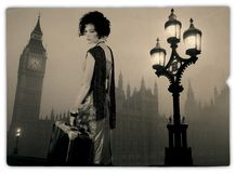 Traveller in London. A young girl with a curly hair, dressed in the outmoded clothes, holds an old suitcase in a hand and looks a sorrowful look in London Royalty Free Stock Photography