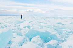 Traveller looks to a field of ice covering Baikal lake in winter. Ice had been broken after strong winter wind Royalty Free Stock Image