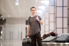 Traveller with luggage at conveyor belt. Portrait of young handsome traveller man in 20s leaving arrivals lounge of airport terminal building after collecting Stock Image