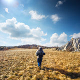 Traveller man with a backpack walks on autumnal plain with dry g Royalty Free Stock Images
