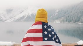 Traveller man with flag of America standing in the snow-covered mountains near beautiful lake. Hiker looking at the