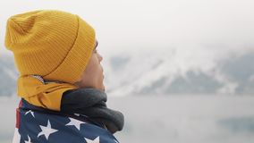 Traveller man with flag of America standing in the snow-covered mountains near beautiful lake. Hiker looking at the. Beautiful nature stock video