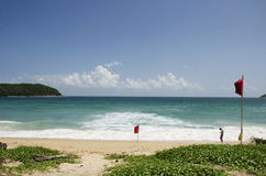 Traveller man stand and play mobile on the Nai Harn beach in Phu Stock Photos