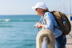 Traveller on pier. Pretty female traveller standing on pier looking at the water Stock Images